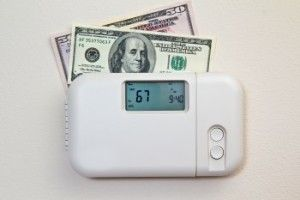 100 dollar bills sticking out of a thermostat