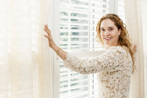 Woman adjusting window blinds