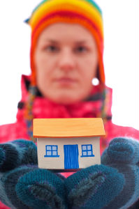 Person in hat and mittens holding a model house