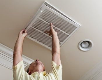 Man placing grate over AC vent