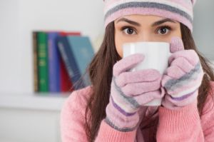 Woman holding a mug and bundled up in a cap and gloves in the house